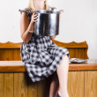 Woman holding hot cooking pot in kitchen - Stock Photo