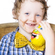 Young boy holding chocolate egg - Stock Photo