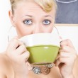 Attractive blonde woman drinking green tea — Stock fotografie