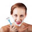 Funny portrait of a woman shaving face with razor — Stockfoto
