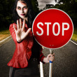 Zombie girl holding stop sign at dead end - Stock Photo