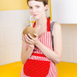 Woman drinking coconut milk in kitchen - Stock Photo