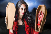 Female Halloween zombie holding undead hand — Stockfoto