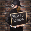Back to school teacher holding blackboard and chalk - Stock Photo