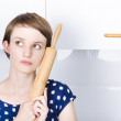 Cute bakery girl holding rolling pin in thought - Stock Photo