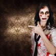 Eerie woman pointing to Halloween copyspace - Stock Photo