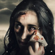 Grim face of horror crying tears of blood - Stock Photo
