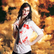 Hot zombie business woman on fire background - Stock Photo