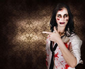 Eerie woman pointing to Halloween copyspace — Stock Photo