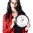 Scary halloween woman holding clock - Stockfoto