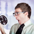 Stressed male office worker holding overtime clock - Stock Photo