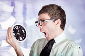 Stressed male office worker holding overtime clock — Stock Photo