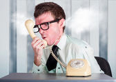 Unhappy nerd businessman yelling down retro phone — Stock Photo