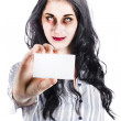 Scary female zombie handing over business card - Stock Photo