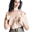 Zombie woman with thumbs up - Stock Photo