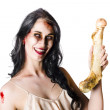 Halloween zombie holding human bone - Stock Photo