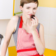 Stock Photo: Woman in Apron Eating Cake