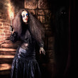 Female jester walking inside dark castle stairwell — Photo