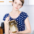 Woman in kitchen with sugar jar - Stock Photo