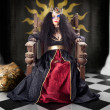 Fashion queen in crown sitting in jester court - Stock Photo