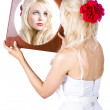Blond woman looking in mirror — Stockfoto