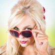Stock Photo: Blond lady wearing UV protective sunshades outside