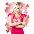 Smiling romantic blond female hugging love heart — Stockfoto