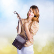 Stock Photo: Young retro fashion model holding leather handbag