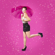 Smiling female model dancing in falling rain — Stock Photo