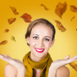 Elegant female model catching autumn leaves — Stock Photo