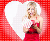 Surprised attractive girl with heart gift box — Stockfoto