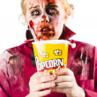 Stock Photo: Zombie womwatching scary movie with popcorn