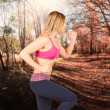 Fitness woman running in forest location - Stock Photo