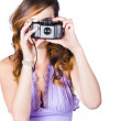 Woman with camera on white background — Stock Photo