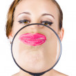 Woman kissing magnifying glass — Stock Photo
