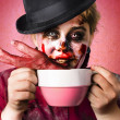 Stock Photo: Scary female zombie drinking handmade soup