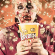 Fearful zombie watching slasher flick. Scary film - ストック写真