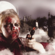 Stock Photo: Zombie with gun in graveyard. Full moon nightmare