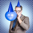 Birthday businessman blowing up smiling balloon — Stock Photo