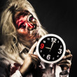 Stock Photo: Late zombie womholding clock. Passing time