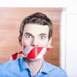 Businessman in silence with red warning tape — Stock Photo
