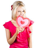 Cute woman biting big red love heart — Stock Photo