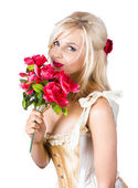 Adorable florist woman smelling red flowers — Stock Photo