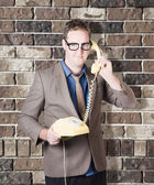 Humorous male nerd chatting business on phone — Stock Photo
