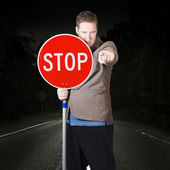Business man holding road stop sign — Stock Photo