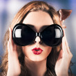 Face of a surprised pinup girl in funny sunglasses — Stock fotografie