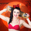 Stock Photo: Retro pinup girl holding old wooden skateboard