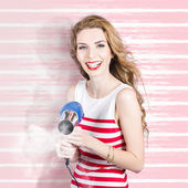 Smiling stylist with hair dryer at beauty salon — Stock Photo