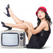 Lovely asian pinup girl posing on vintage tv set — Stock Photo
