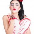 Isolated pin up woman holding a heart shaped sign — Stok fotoğraf